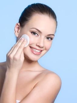 Ragazza teenager felice che si prende cura della sua pelle fresca e sana del viso con disco di tampone di cotone sull'azzurro