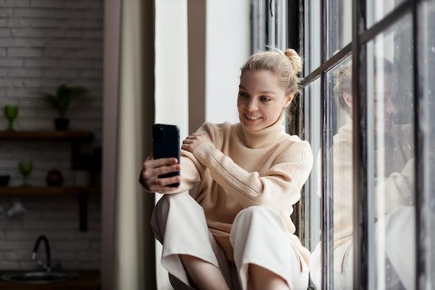 Счастливая девочка-подросток проверяет социальные медиа, держа смартфон дома. использование мобильного телефона для покупок в интернете, заказ доставки. фото высокого качества