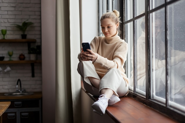 Happy teen girl checking social media holding smartphone at home. using mobile phone shopping online, ordering delivery. high quality photo