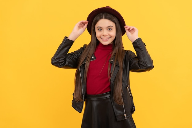 Happy teen girl in hat and leather jacket, trend.