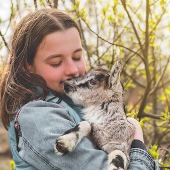 Счастливая девочка-подросток, держащая козу на руках