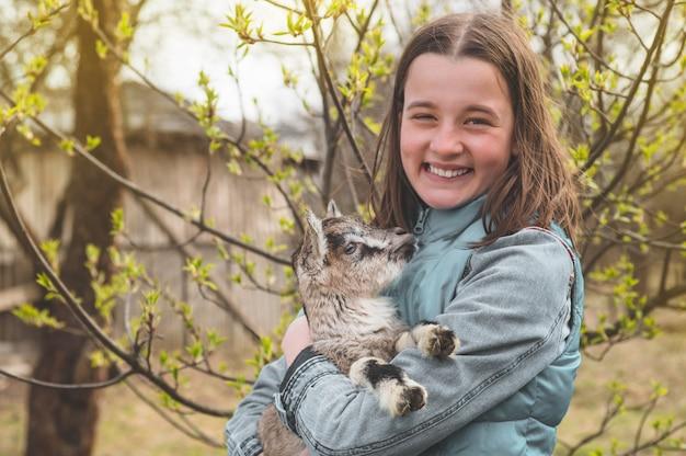 ヤギを両腕に抱えて幸せな十代の少女