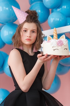 Happy teen girl holding unicorn layered cake decorated with meringues close-up.