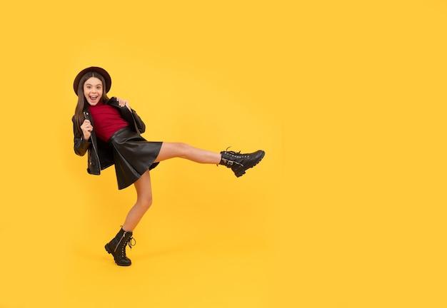 帽子と革の服を着た幸せな十代の少女は、広い一歩を踏み出し、スペースをコピーし、楽しんでいます。