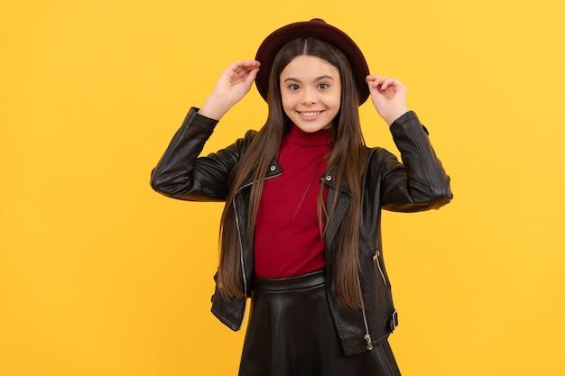 帽子と革のジャケット、トレンドの幸せな十代の少女。