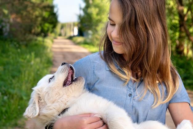 屋外で夏の日に彼女の手でそれを保持しているピレネー山脈の山犬のかわいい子犬と遊ぶ幸せな十代の少女