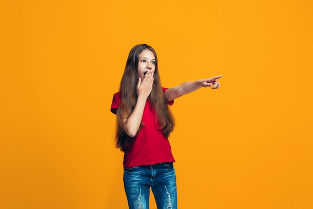 The happy teen girl pointing to something