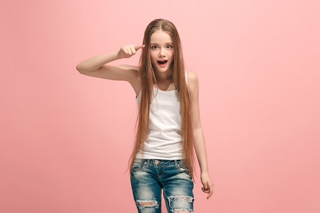 The happy teen girl pointing to you, half length closeup portrait on pink.