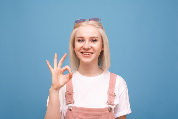 幸せな十代の少女はokの兆候を示していますカメラと笑顔を見て、青い背景に分離されたかわいいカジュアルな服とサングラスを着ています。