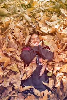Happy teen girl smiling in a black dress lay down in the autumn of dry leaf.