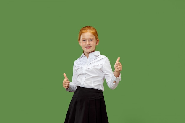 Счастливая девушка стоит и улыбается на зеленом фоне