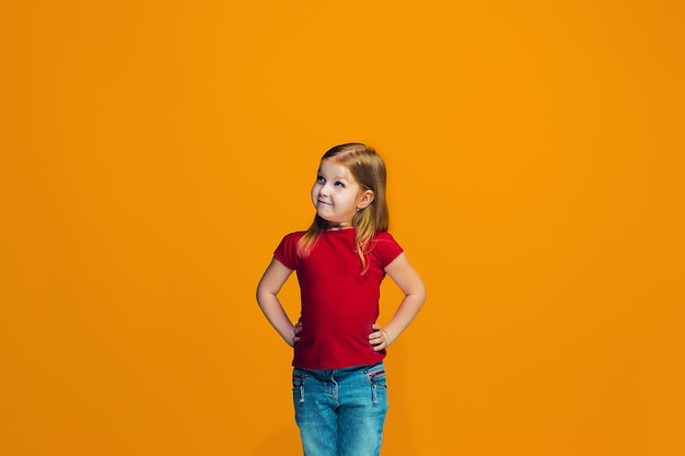 The happy teen girl standing and smiling against orange space.