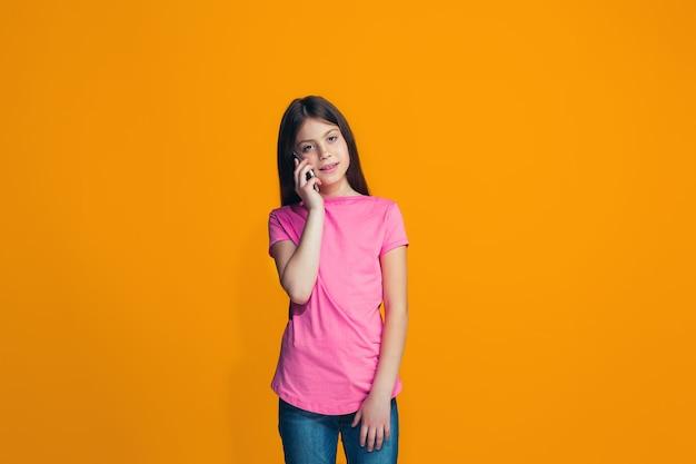 La ragazza teenager felice in piedi e sorridente contro l'arancio.