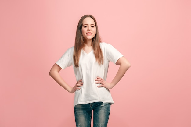 The happy teen girl standing and smiling against pink wall