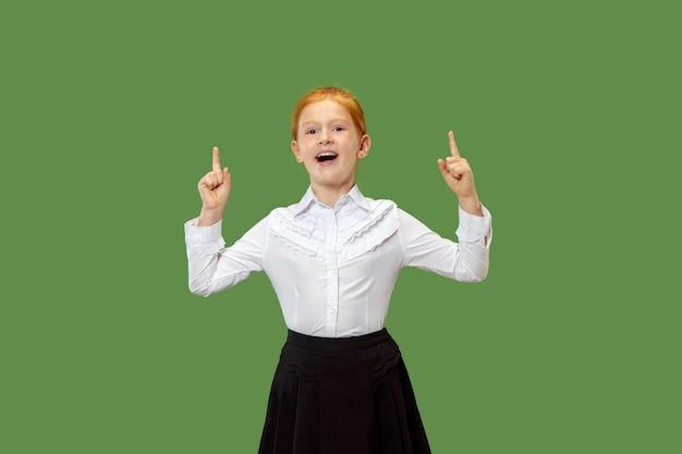 Счастливый подросток девушка стоя, улыбаясь и указывая вверх изолированные на модном зеленом фоне студии. красивый женский поясной портрет. человеческие эмоции, концепция выражения лица.