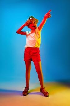Счастливая девушка-подросток стоит, улыбается и указывает вверх над модной синей неоновой студией