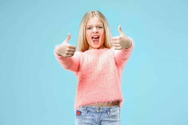 Счастливый подросток девушка стоя, улыбаясь, изолированные на модном синем пространстве. красивый женский портрет. молодые удовлетворить девушку знаком ок. человеческие эмоции, концепция выражения лица
