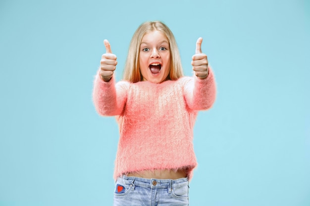 トレンディな青いスタジオで孤立した笑顔、立っている幸せな十代の少女。