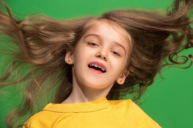 立っている幸せな十代の少女、トレンディな緑に孤立した笑顔。美しい女性の肖像画。