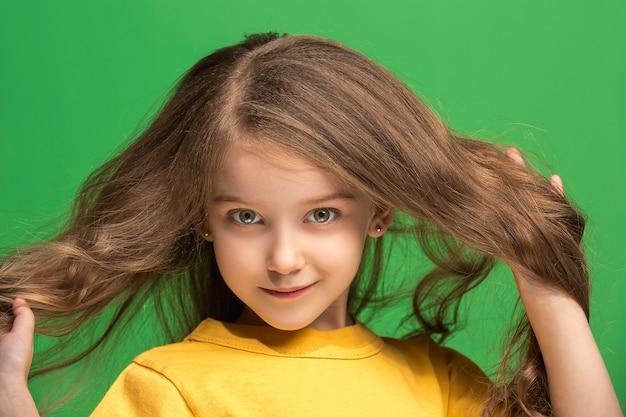서, 유행 녹색 스튜디오 배경에 고립 웃 고 행복 한 십 대 소녀. 아름다운 여성의 초상화. 젊은 만족 소녀. 인간의 감정, 표정 개념. 전면보기.
