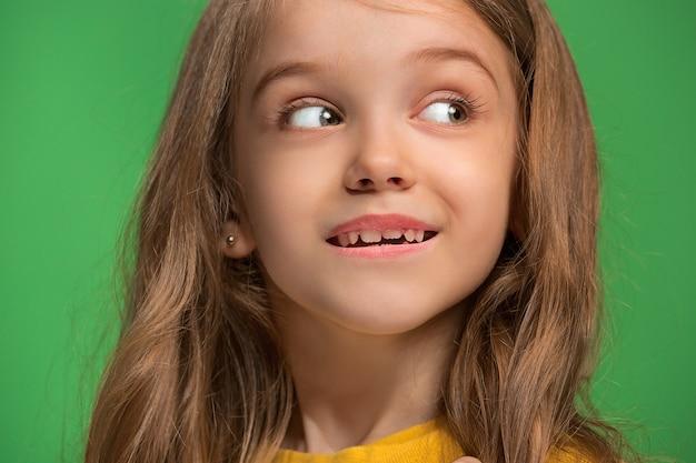 トレンディな緑のスタジオで孤立した笑顔、立っている幸せな十代の少女。