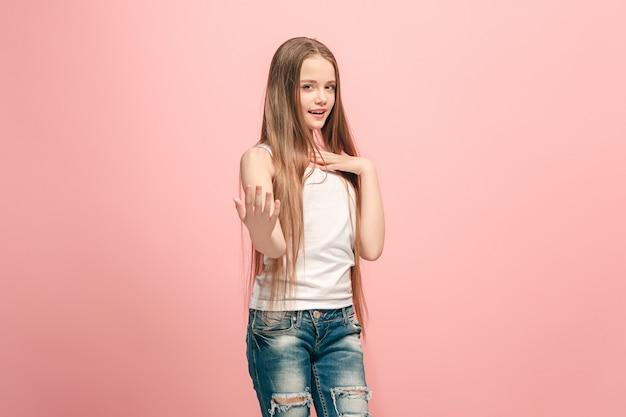 トレンディなピンクのスタジオの背景に孤立した笑顔、立っている幸せな十代の少女。美しい女性の半身像
