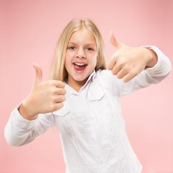 서, 유행 핑크 스튜디오 배경에 고립 웃 고 행복 한 십 대 소녀. 아름다운 여성의 초상화. 젊은 만족 여자 기호 확인.