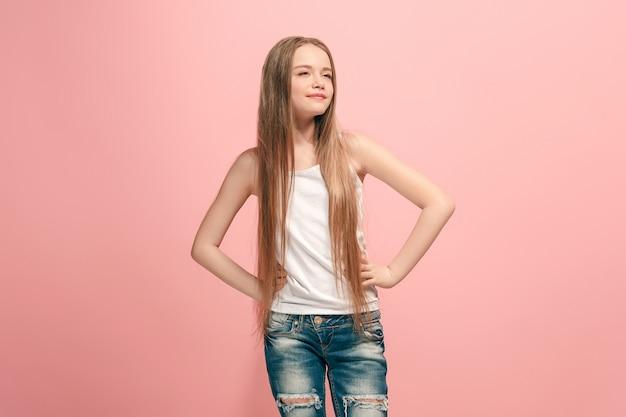 Счастливый подросток девушка стоя, улыбаясь, изолированные на модном розовом фоне студии.