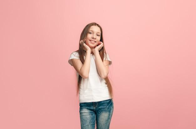 Счастливая девочка-подросток стоя, улыбаясь изолированной на модной розовой стене студии