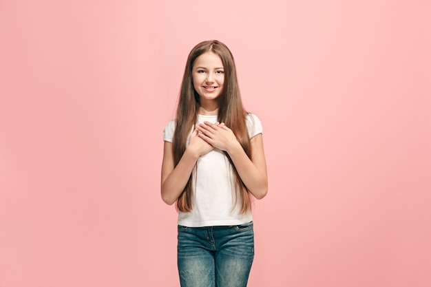 Счастливая девочка-подросток стоя, улыбаясь изолированной на модной розовой студии