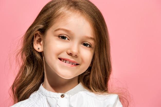 トレンディなピンクの壁に孤立して笑顔、立っている幸せな十代の少女。美しい女性の肖像画。若い満足の女の子。人間の感情、表情の概念。正面図。