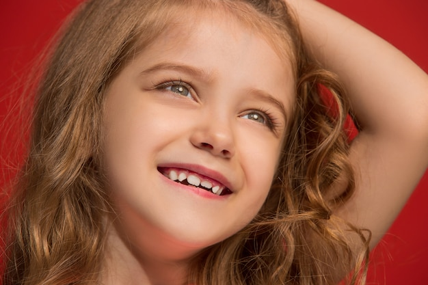 立っている幸せな十代の少女、トレンディな赤で孤立した笑顔。美しい女性の肖像画。