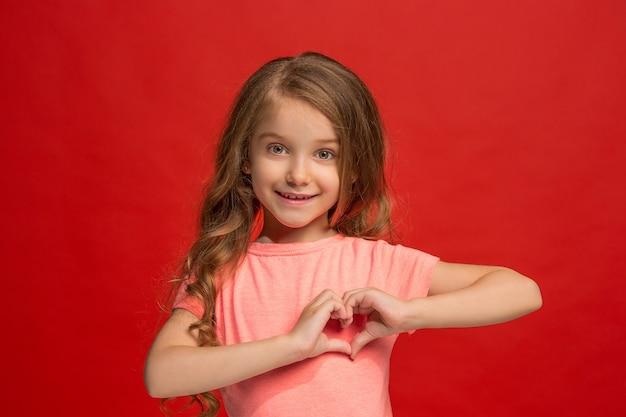 トレンディな赤いスタジオの背景に孤立した笑顔、立っている幸せな十代の少女。美しい女性の肖像画。若い満足の女の子。