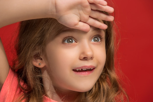 トレンディな赤いスタジオの背景に孤立した笑顔、立っている幸せな十代の少女。若い満足の女の子。正面図。