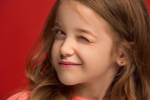 행복 한 십 대 소녀 서, 웃 고 유행 빨간 스튜디오 배경에 고립.