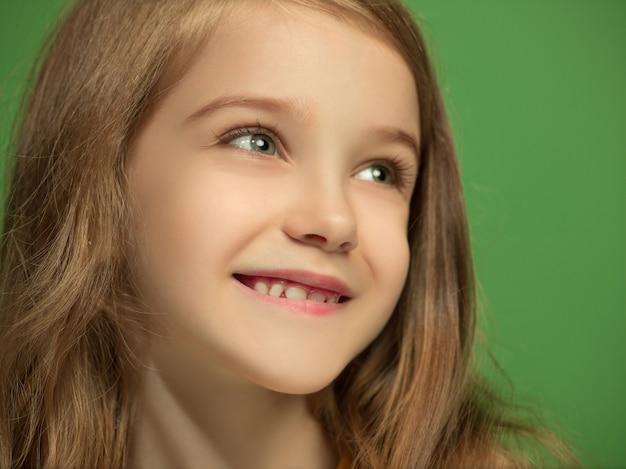 Felice ragazza adolescente in piedi, sorridente isolato su sfondo verde alla moda per studio. bellissimo ritratto femminile. i giovani soddisfano la ragazza. emozioni umane, concetto di espressione facciale. vista frontale.