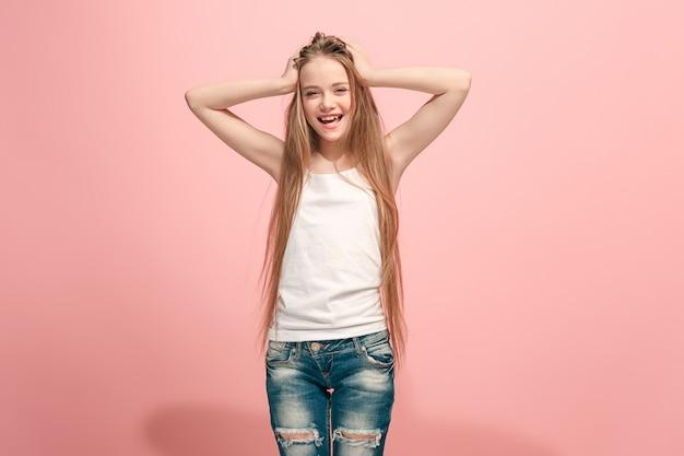 Ragazza teenager felice in piedi, sorridente isolato su sfondo rosa alla moda per studio. bellissimo ritratto femminile a mezzo busto. emozioni umane, concetto di espressione facciale.