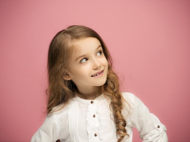 Felice ragazza adolescente in piedi, sorridente isolato su sfondo rosa alla moda per studio. bellissimo ritratto femminile. i giovani soddisfano la ragazza