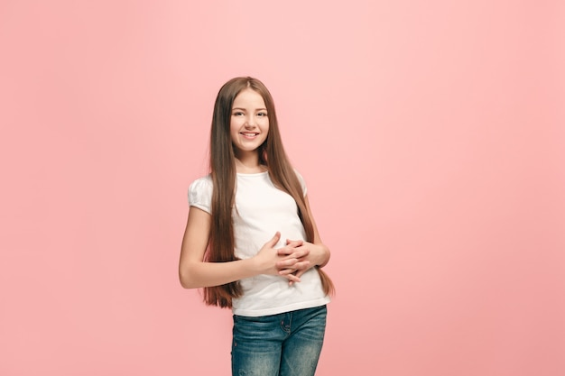 Happy teen girl standing, smiling isolated on trendy pink studio background.
