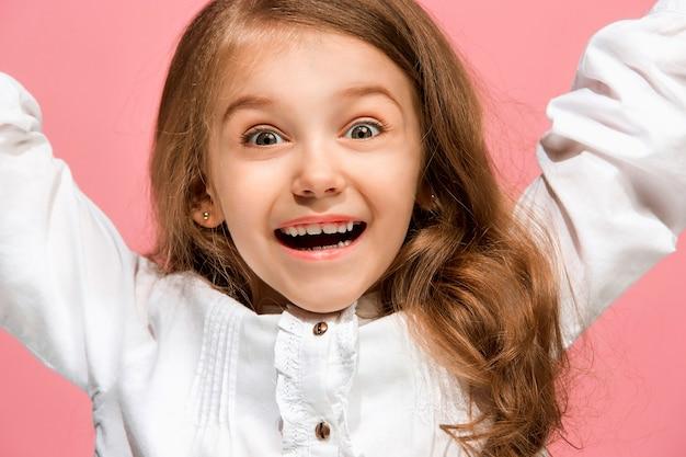 Ragazza teenager felice in piedi, sorridente isolato su studio rosa alla moda