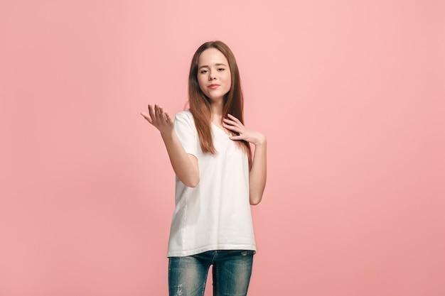 Ragazza teenager felice in piedi, sorridente isolato su studio rosa alla moda.