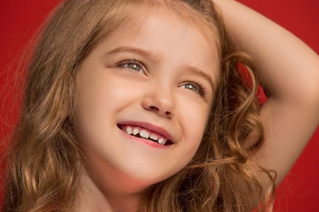 Felice ragazza adolescente in piedi, sorridente isolato sul rosso alla moda. bellissimo ritratto femminile.