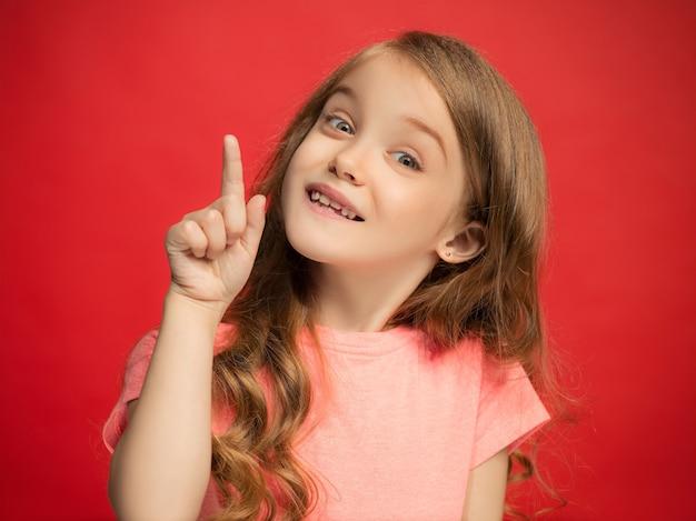 Ragazza teenager felice che sta, sorridente isolata sulla parete rossa alla moda dello studio