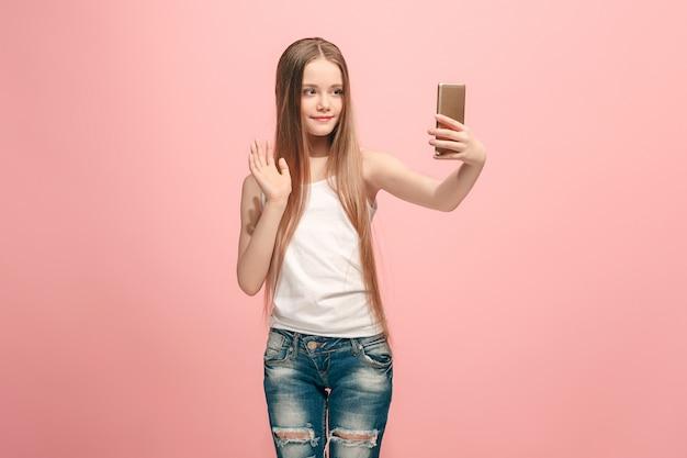 幸せな十代の少女が立って、ピンクに笑みを浮かべて、携帯電話で自分撮り写真を作っています。人間の感情、表情の概念