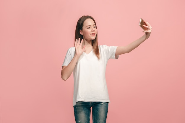 立っている、ピンクのスタジオで笑って幸せな十代の少女