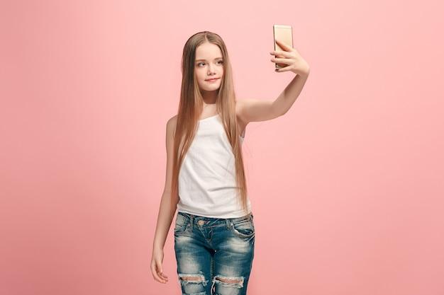 ピンクの壁に笑みを浮かべて、携帯電話で自分撮り写真を作って立っている幸せな十代の少女。人間の感情、表情の概念。正面図。
