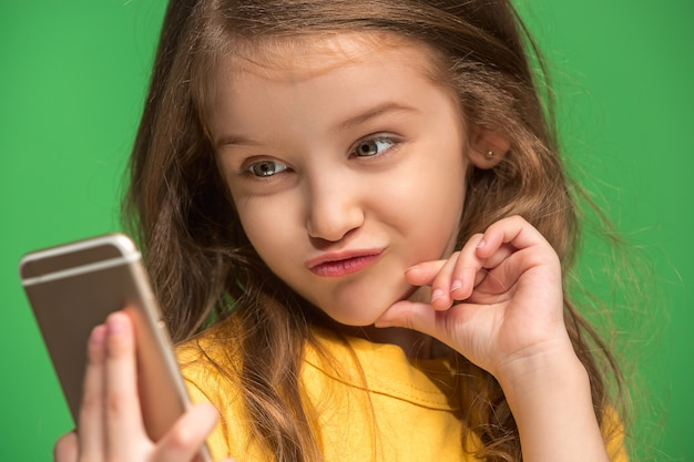 トレンディな緑の上に携帯電話で笑って立っている幸せな十代の少女。美しい女性の半身像
