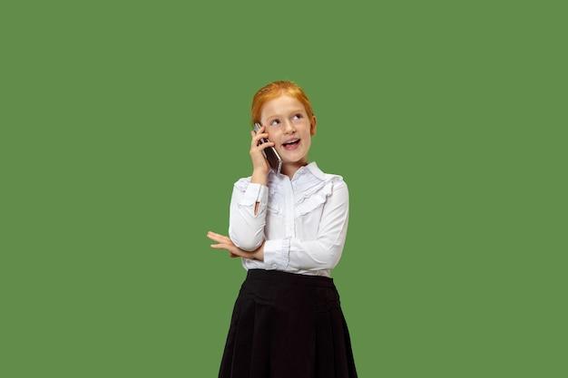 トレンディな緑のスタジオの背景に携帯電話で笑って立って、幸せな十代の少女。美しい女性の半身像。人間の感情、表情の概念。