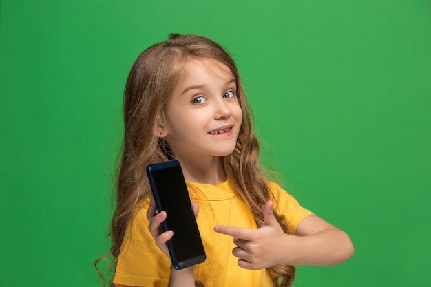 トレンディな緑のスタジオの背景の上に携帯電話で笑って立って、幸せな十代の少女。美しい女性のハーフレングスの肖像画。人間の感情、顔の表情の概念。