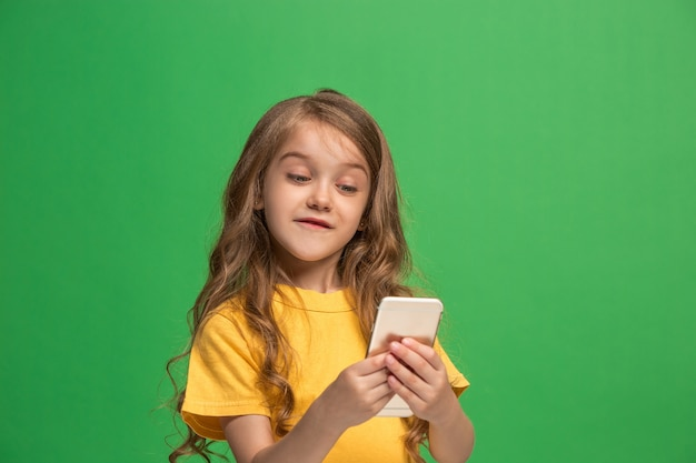 トレンディな緑のスタジオの背景の上に携帯電話で笑って立って、幸せな十代の少女。